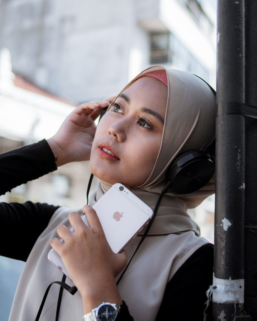 Muslim woman listens to AudioBlog while outdoors