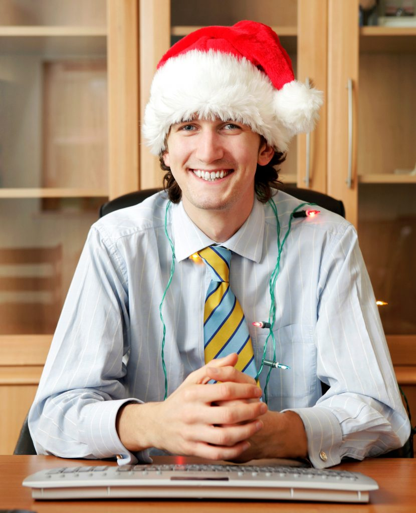 man in santa hat ready for holiday work party