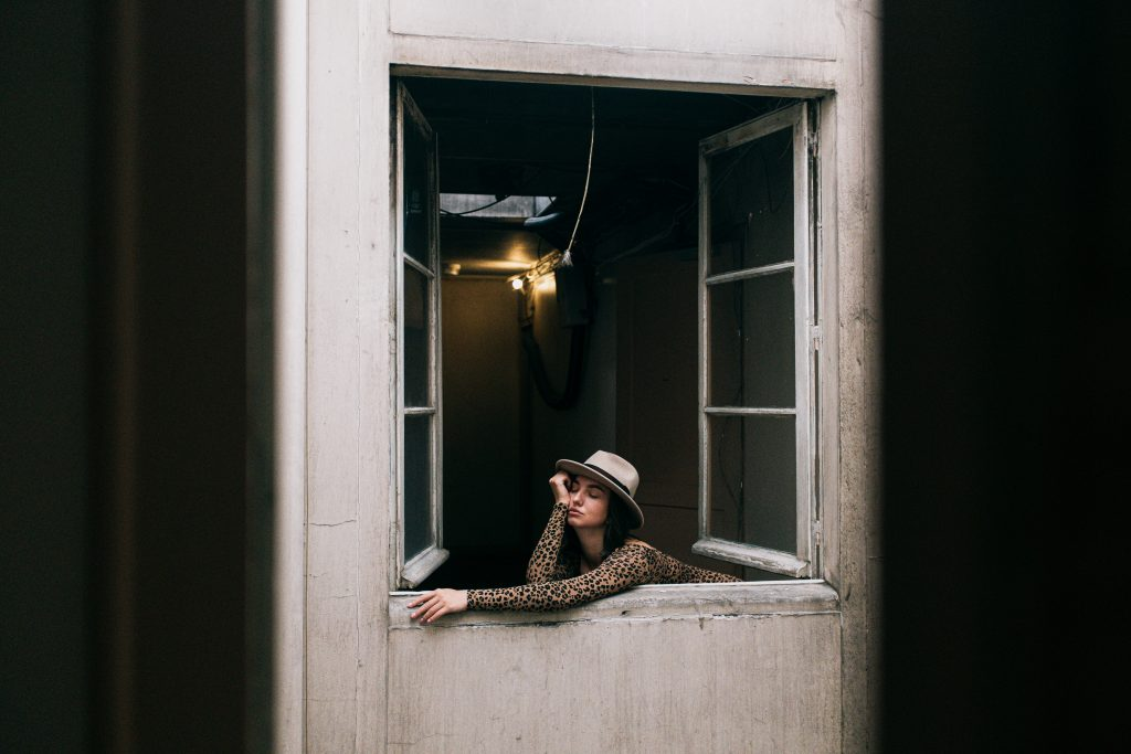 woman in window coping with pandemic grief