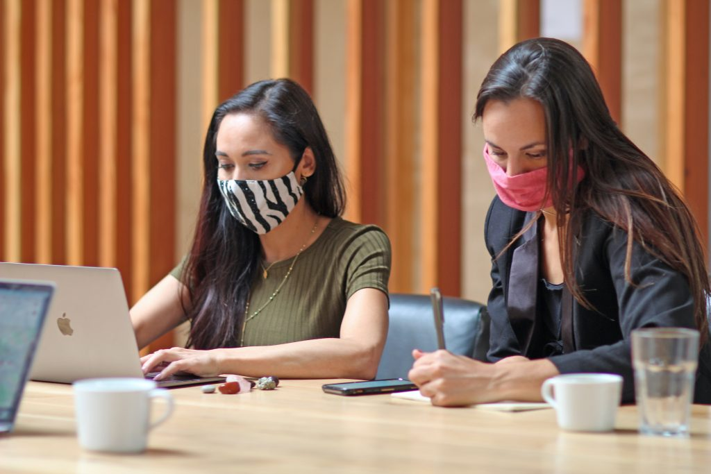 two women working in masks doing awkward communication